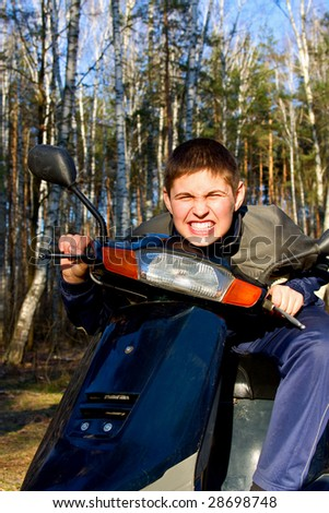 Boy on scooter in the woods - stock photo