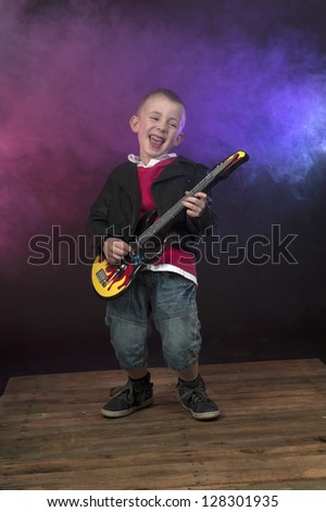 boy on stage with smoke, playing the guitar - stock photo