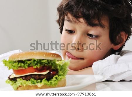Boy on temptation with burger - stock photo