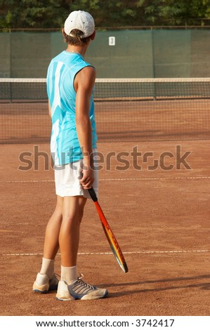 boy on tennis court awaiting the opponent - stock photo