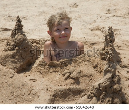 boy on the beach buried in sand on a summer day - stock photo