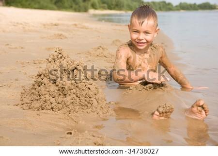 Boy on the beach digging himself - stock photo