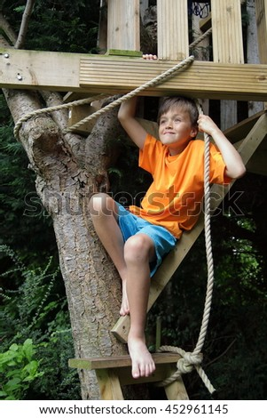 Boy on the ladder of his treehouse - stock photo