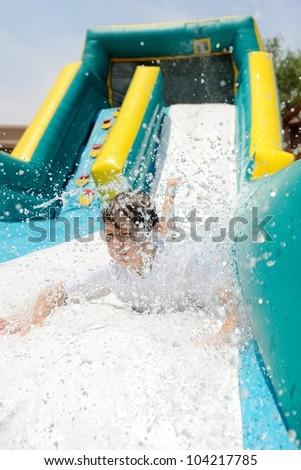 Boy on Water Slide. Boy making a splash as he slides down a water slide. - stock photo