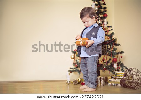 Boy opening present in front of christmas tree - stock photo