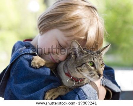Boy out of focus and focus on cat - stock photo