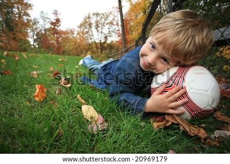 Boy outdoors lying on green grass with soccer ball under his head, looking at camera, smiling. - stock photo