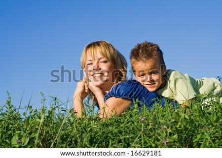 Boy outdoors on the grass with his mother in summer time