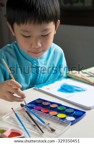 Boy Painting Coloring Book In The Room