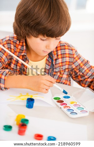 Boy painting. Little boy relaxing while painting with watercolors sitting at the table - stock photo