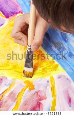 boy painting the sun with fluorescent colors, sunset scene - stock photo