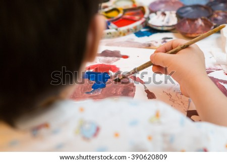 Boy painting with brush.