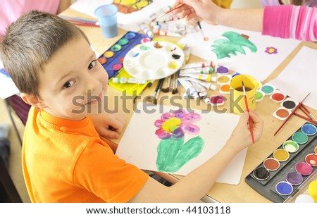 boy painting with watercolor - stock photo