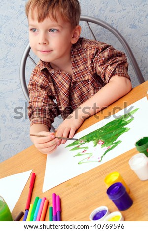 boy paints a Christmas picture - stock photo