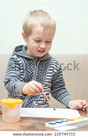 Boy paints watercolors - stock photo