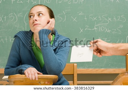 Boy passing girl a letter in class - stock photo
