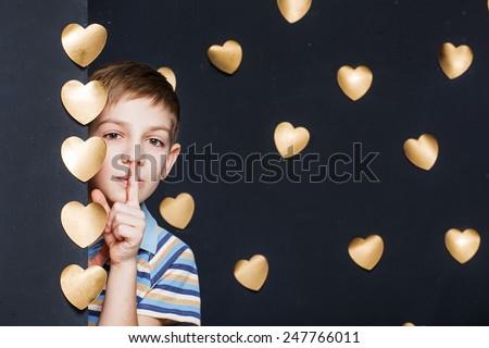 Boy peeking on golden hearts dark background - stock photo