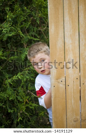 Boy peeks with concern from behind a door - stock photo