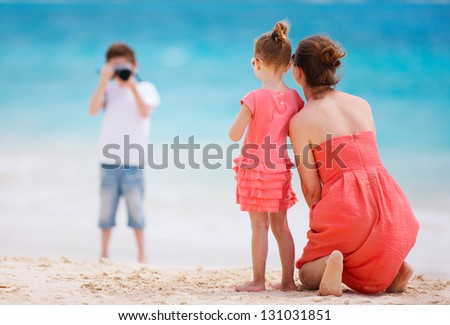 Boy photographing his mother and little sister at tropical beach - stock photo