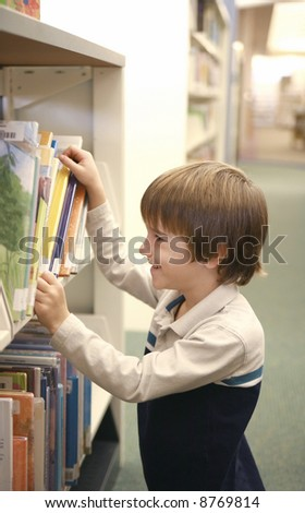 Boy Picking Out a Library book - stock photo