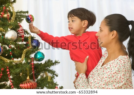Boy placing ornaments on tree with mom - stock photo