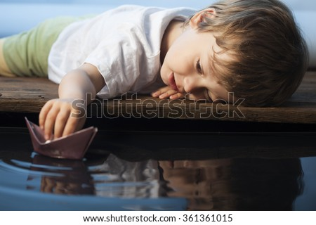 boy play in paper ship in water puddel