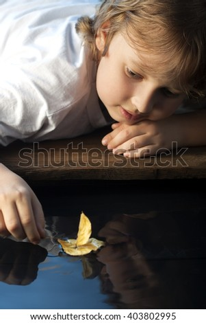 boy play in paper ship in water puddle - stock photo