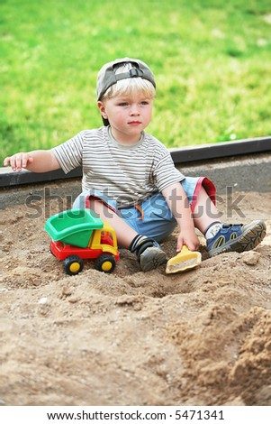 boy play sand with color toy car - stock photo