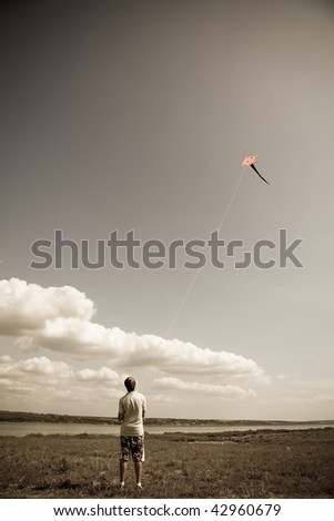 Boy play with fly kite. Photo in vintage yellow style. - stock photo