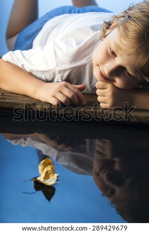 boy play with leaf ship in water - stock photo