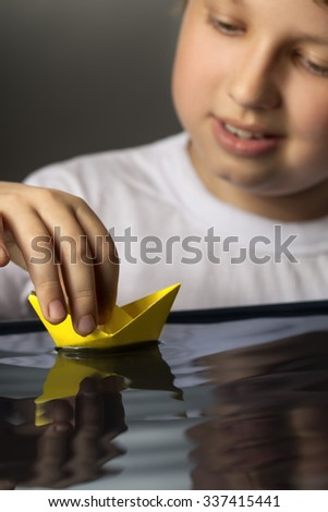 boy play with leaf ship in water (focus on ship) - stock photo