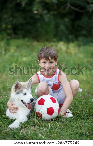 Boy play with malamute puppy; Outdoor portrait