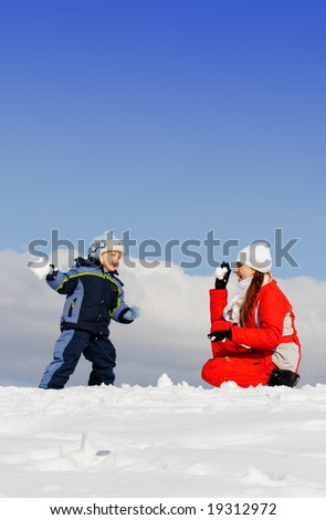 Boy played with mother in winter park. Snow. Blue sky - stock photo