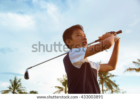 Boy player golf swing shot on course in summer - stock photo