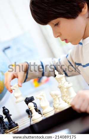 boy playing a game of chess, the development of logical thinking - stock photo