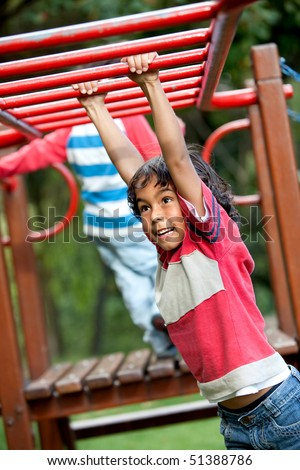 Boy playing at the park on the monkey bars - stock photo