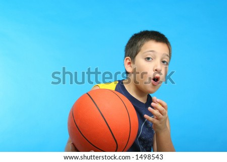 Boy playing basketball blue background.