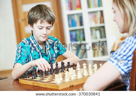 boy playing chess at home - stock photo