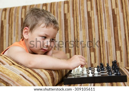 Boy playing chess on the sofa at home - stock photo