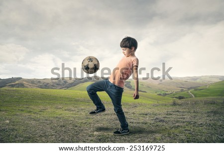 Boy playing football in the countryside  - stock photo