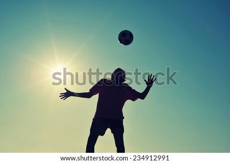 Boy playing football on beach at sunset - stock photo