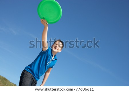 Boy playing frisbee on beach - stock photo
