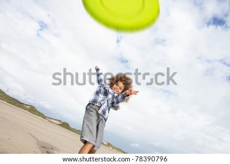 Boy playing frisbee on beach - stock photo