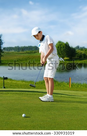 Boy playing golf and hitting by putter on green - stock photo