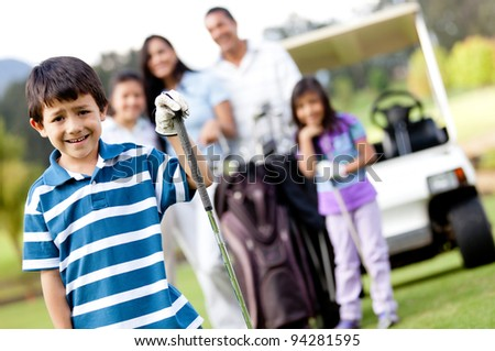 Boy playing golf with his family at the background - stock photo