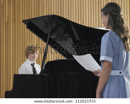 Boy playing grand piano with female friend - stock photo