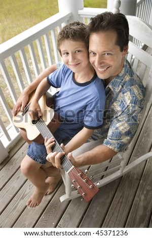 Boy playing guitar while sitting on his father's lap. Vertical shot. - stock photo