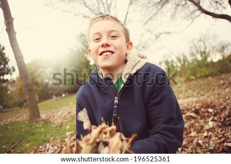 Boy playing in a pile of autumn leaves - stock photo