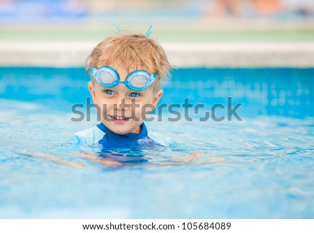 boy playing in a pool of water during the summer