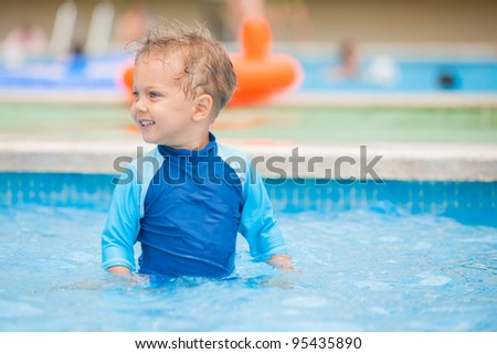 boy playing in a pool of water during the summer - stock photo